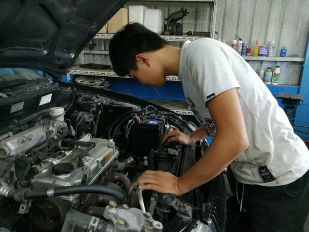 阿軒在汽車修理廠檢查待修的汽車狀況