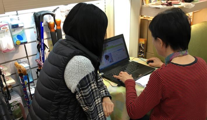 主管指導繡姐(右)將貨品上架網路商店