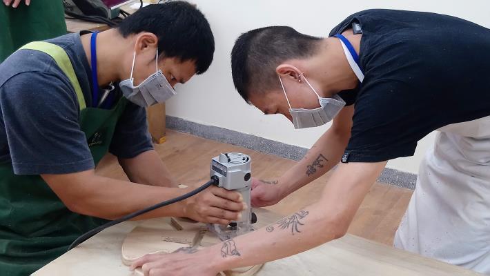 阿德(右)擔任小老師,指導同學操作打磨修邊機具