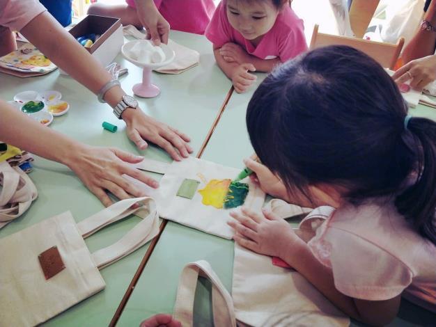 多名小朋友在「凱恩外婆」的親子手作互動課程繪製環保袋。