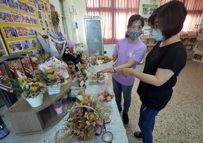 侯美珠(左)運用以往對美感的敏銳度,將木玫瑰變身為有質感的花藝作品,讓遊客驚艷不已。.JPG